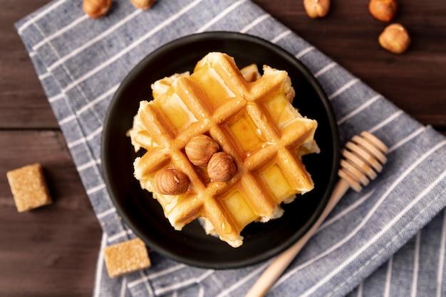 Bovenaanzicht van hazelnoten en honing bovenop wafels op plaat