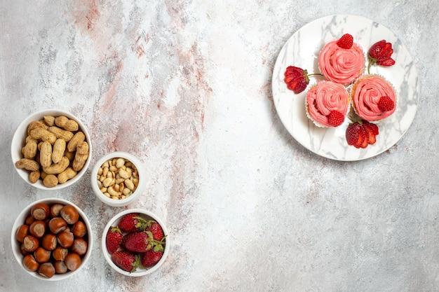 Bovenaanzicht van hazelnoten en pinda's met aardbeien op het witte oppervlak