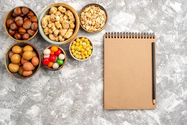Bovenaanzicht van hazelnoten en pinda's met snoepjes en kladblok op witte ondergrond