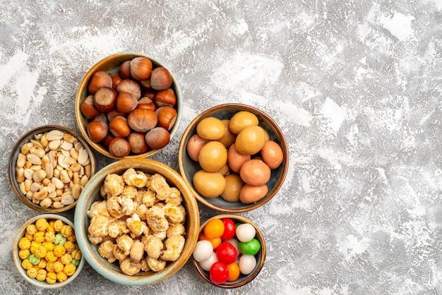 Bovenaanzicht van hazelnoten en pinda's met snoepjes op witte ondergrond