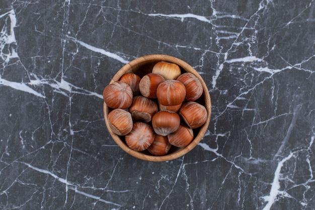 Bovenaanzicht van hazelnoten in houten kom.