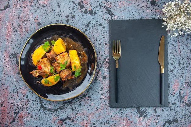 Bovenaanzicht van heerlijk diner met vlees aardappelen geserveerd met groen in een zwarte plaat en bestek ingesteld op snijplank bloem op mix kleuren achtergrond