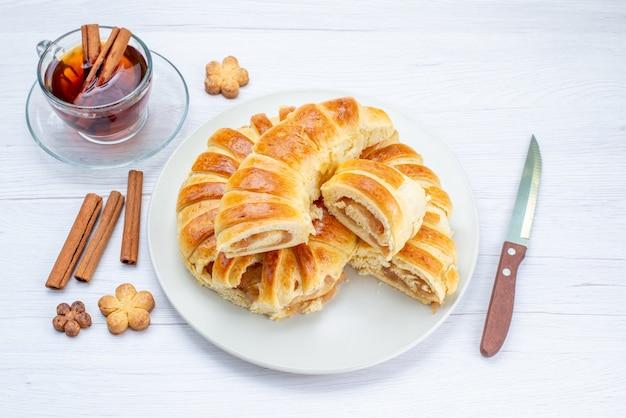 Bovenaanzicht van heerlijk gebakken gebak met zoete vulling gesneden en geheel samen met koekjes en thee op licht bureau, koekjes koekjes gebak cake thee