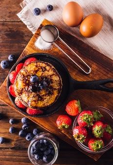 Bovenaanzicht van heerlijk ontbijt van pannenkoeken geserveerd met aardbeien en bosbessen
