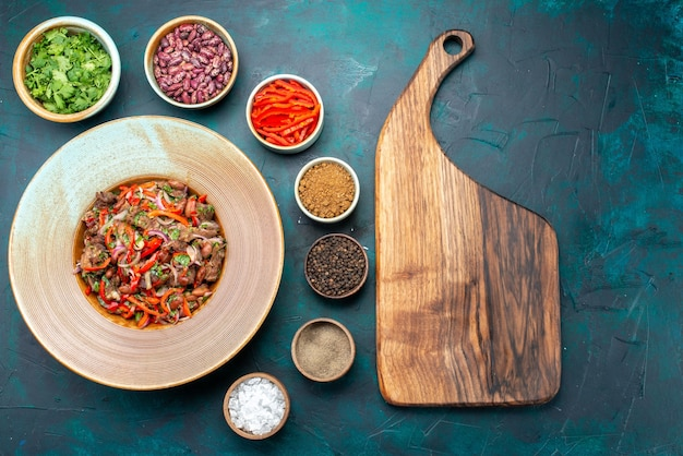 Bovenaanzicht van heerlijk vlees eten met groenten in plaat, samen met greens en kruiden op donkerblauw, groente vleesmeel