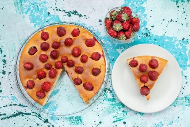 Bovenaanzicht van heerlijke aardbeientaart gesneden en hele heerlijke cake samen met verse rode aardbeien op helderblauw bureau, zoete bessentaart bakken