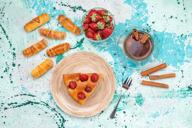 Bovenaanzicht van heerlijke aardbeientaart gesneden lekkere cake met theekaneel en armbanden op helderblauw, bessentaart zoet bakdeeg