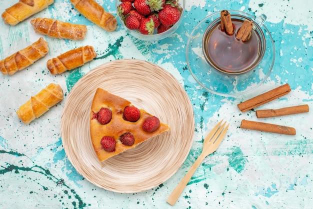 Bovenaanzicht van heerlijke aardbeientaart gesneden lekkere cake met theekaneel en armbanden op helderblauwe, zoete bessentaart