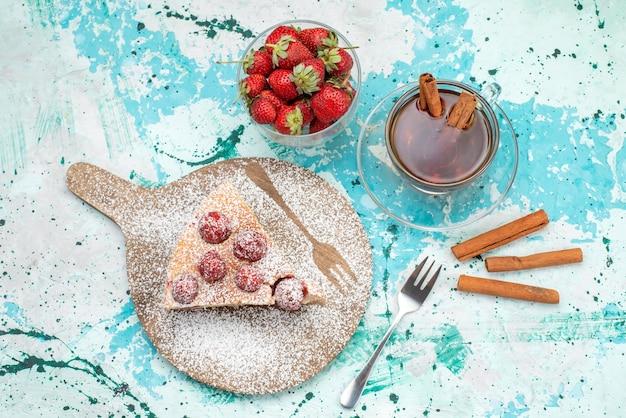 Bovenaanzicht van heerlijke aardbeientaart gesneden lekkere cake suiker gepoederd met thee op helderblauw, bessentaart zoet bakdeeg