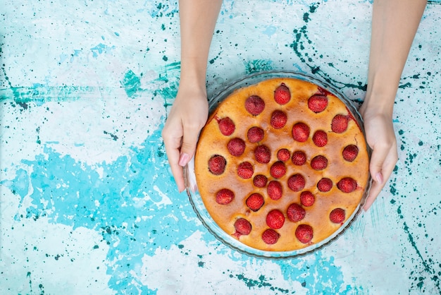 Bovenaanzicht van heerlijke aardbeientaart rond gevormd met fruit bovenop en binnen op blauw bureau, cakedeeg zoet koekje