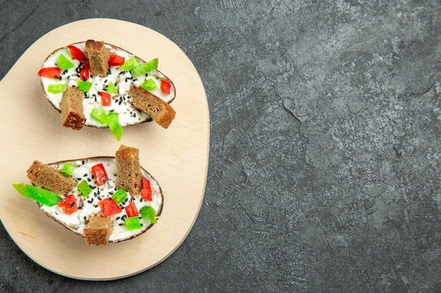 Bovenaanzicht van heerlijke avocado maaltijd met zure room gesneden paprika en stukjes brood op donkergrijs oppervlak
