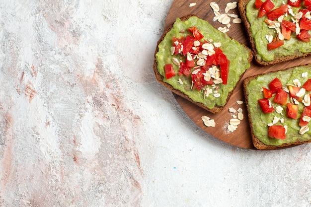 Bovenaanzicht van heerlijke avocado sandwiches met gesneden rode tomaten op witte ondergrond