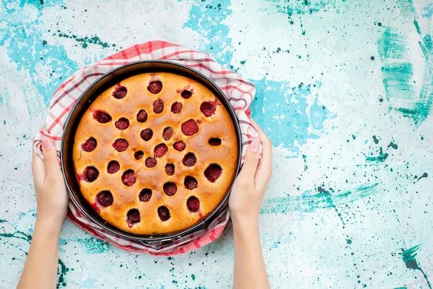 Bovenaanzicht van heerlijke bessentaart gebakken en lekker in de pan op helderblauw, cakekoekdeeg bes zoet