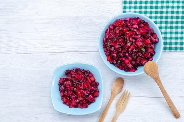 Bovenaanzicht van heerlijke bietensalade gesneden met greens en groenten in blauwe plaat op licht bureau, plantaardige vitamine voedsel gezondheidssalade