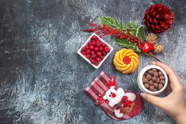 Bovenaanzicht van heerlijke biscuit decoratie accessoire kerstman sok en cornell in een kom dennentakken aan de linkerkant op donkere ondergrond
