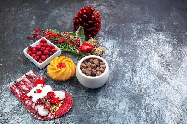 Bovenaanzicht van heerlijke biscuit decoratie accessoire kerstman sok en cornell in een kom dennentakken aan de rechterkant op donkere ondergrond