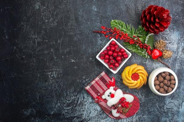 Bovenaanzicht van heerlijke biscuit decoratie accessoire kerstman sok en cornell in een kom dennentakken op donkere ondergrond