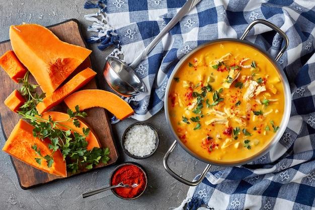 Bovenaanzicht van heerlijke butternut squash kippenborst romige soep in een metalen braadpan op een betonnen tafel