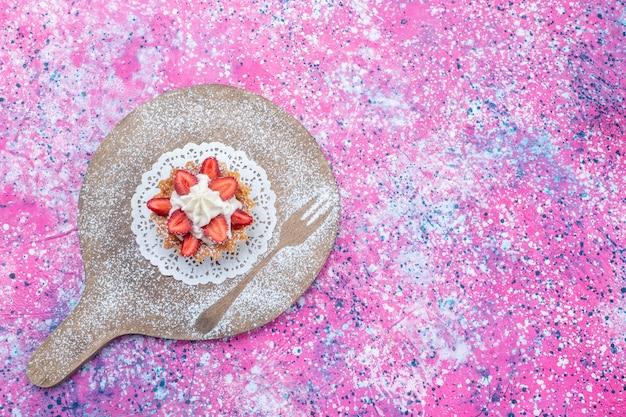 Bovenaanzicht van heerlijke cake met room en gesneden rode aardbeien op helder paars, zoete cake biscuit bakken