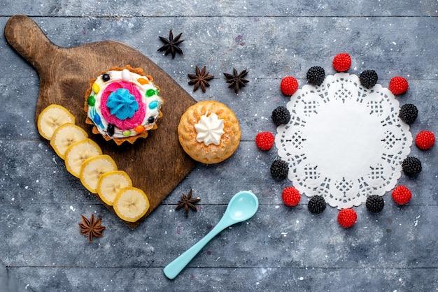 Bovenaanzicht van heerlijke cake met slagroom en snoep, samen met bessen, koekjes, taarten op licht, cake koekje zoet bak kandijsuiker