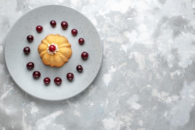 Bovenaanzicht van heerlijke cake met verse kersen in plaat op lichtgrijs bureau, cake crème fruit bakken koekje