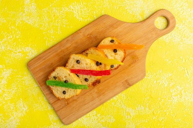 Bovenaanzicht van heerlijke cakeplakken met marmelade op het bruine houten oppervlak en het gele oppervlak