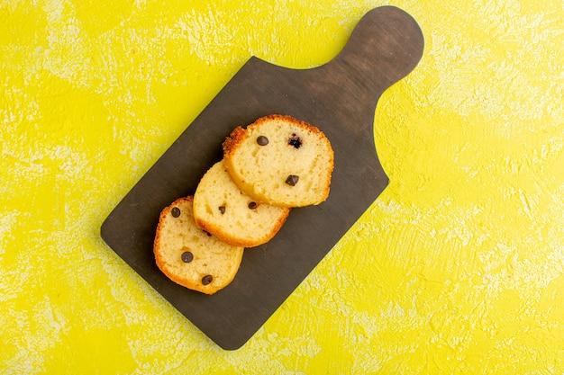 Bovenaanzicht van heerlijke cakeplakken op het bruine houten oppervlak en het gele oppervlak