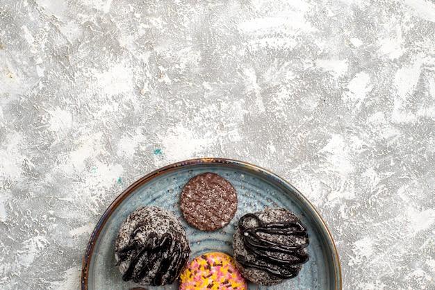 Bovenaanzicht van heerlijke chocolade ballen taarten met koekjes op witte ondergrond