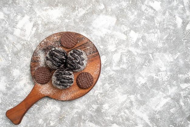 Bovenaanzicht van heerlijke chocolade ballen taarten met koekjes op witte ondergrond Gratis Foto