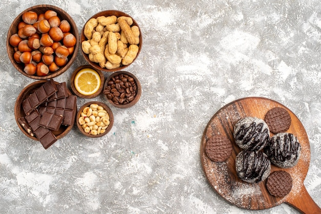 Bovenaanzicht van heerlijke chocoladetaarten met koekjes en pinda's op het witte oppervlak