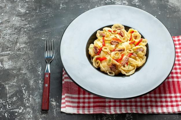 Bovenaanzicht van heerlijke conchiglie met groenten en greens op een bord en mes op rode gestripte handdoek aan de linkerkant op grijze achtergrond