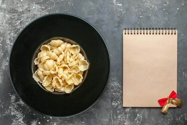 Bovenaanzicht van heerlijke conchiglie op een zwarte plaat en notitieboekje op grijze achtergrond