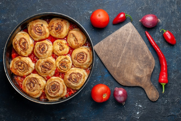 Bovenaanzicht van heerlijke deegmaaltijd met vlees in de pan samen met verse groenten zoals uien, tomaten, paprika's op donker bureau, voedselmaaltijd vlees groente