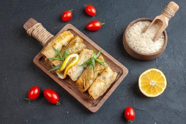 Bovenaanzicht van heerlijke dolmamaaltijd op een houten snijplank geserveerd met citroengroen en rijsttomaten op donkere muur