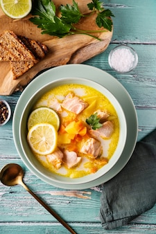 Bovenaanzicht van heerlijke en gezonde zalmsoep met plantaardige room, wortelen en aardappel in groene plaat op rustiek turkoois oppervlak