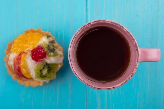 Bovenaanzicht van heerlijke fruittaart met een kopje thee op een blauwe houten achtergrond