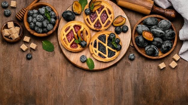 Bovenaanzicht van heerlijke fruittaarten met pruimen en kopieer de ruimte