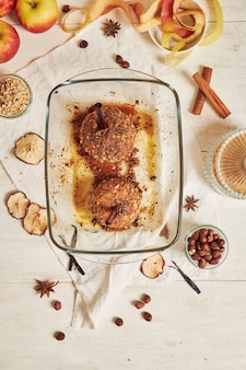 Bovenaanzicht van heerlijke gebakken appel met noten en kaneel voor kerstmis op een witte tafel
