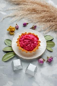 Bovenaanzicht van heerlijke gebakken cake met roze room en chocolaatjes op licht, cake zoete bak cream tea