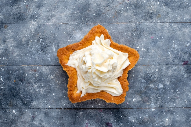 Bovenaanzicht van heerlijke gebakken cake stervormig met witte lekkere room binnen op licht bureau, cake bak suiker zoete cream tea