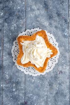Bovenaanzicht van heerlijke gebakken cake stervormig met witte lekkere room binnen op licht bureau, cake bak suiker zoete room