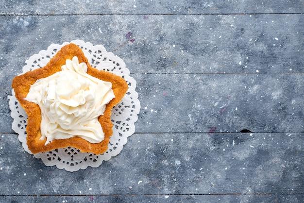 Bovenaanzicht van heerlijke gebakken cake stervormig met witte lekkere room binnen op licht bureau, cake bak zoet roomkoekje