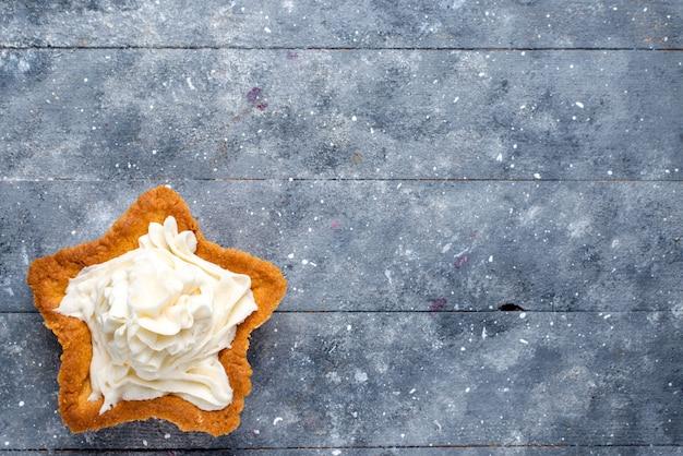Bovenaanzicht van heerlijke gebakken cake stervormig met witte lekkere room binnen op licht bureau, cake bak zoete cream tea