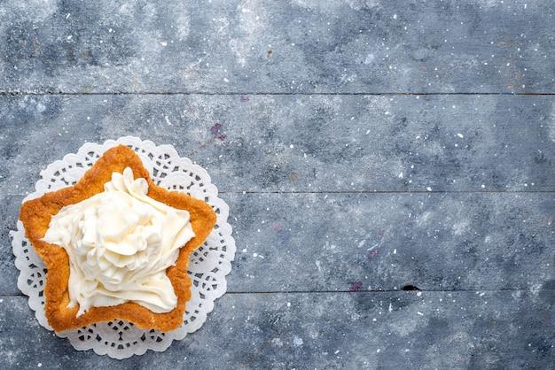Bovenaanzicht van heerlijke gebakken cake stervormig met witte lekkere room binnen op licht bureau, cake suiker zoete cream tea