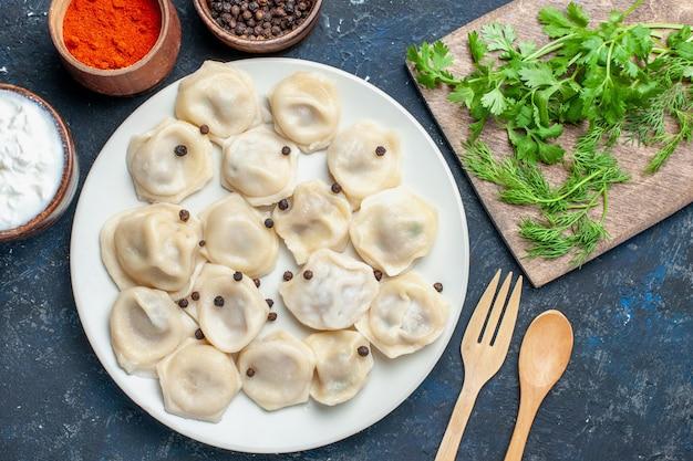 Bovenaanzicht van heerlijke gebakken dumplings in plaat samen met peper en greens op donkere vloer, maaltijd eten diner vlees calorie