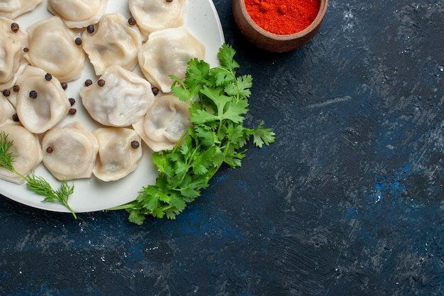 Bovenaanzicht van heerlijke gebakken dumplings in plaat samen met peper en greens op donkergrijs bureau