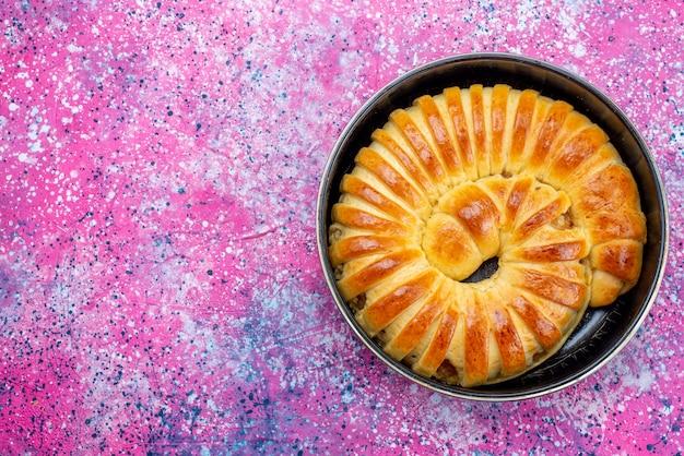 Bovenaanzicht van heerlijke gebakken gebakjesarmband gevormd in pan op licht, gebak koekjeskoekje zoete suiker