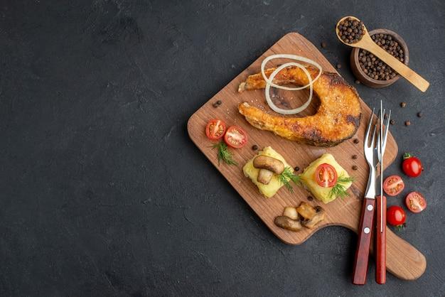 Bovenaanzicht van heerlijke gebakken vis en champignons tomaten groenen op houten snijplank bestekset peper op zwarte ondergrond