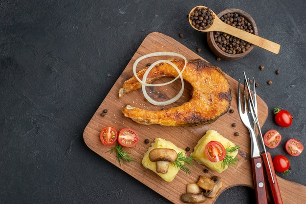 Bovenaanzicht van heerlijke gebakken vis en champignons, tomatengroenten op houten snijplank, bestekset peper op zwart oppervlak