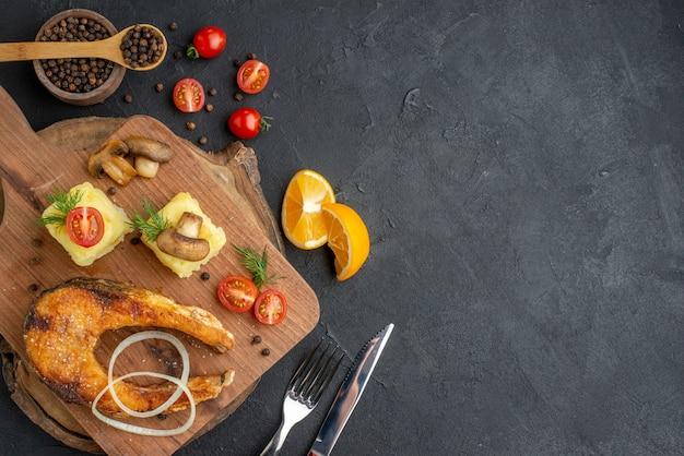 Bovenaanzicht van heerlijke gebakken vis en champignons, tomatengroenten op snijplank, bestekset peper op zwart oppervlak